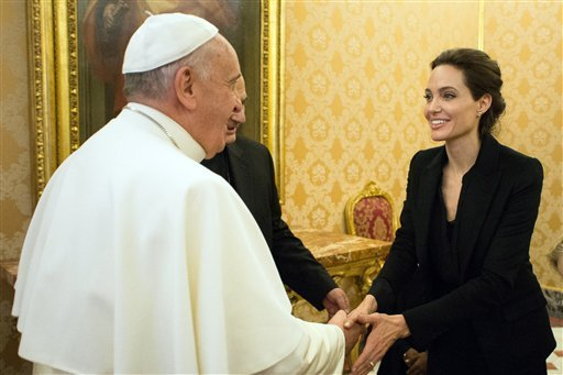 """Pope Francis greets Angelina Jolie at the Vatican Thursday. The actress, director and U.N. special envoy met briefly with Pope Francis in the Apostolic Palace after screening her film """"Unbroken"""" to some Vatican officials and ambassadors. The Associated Press"""