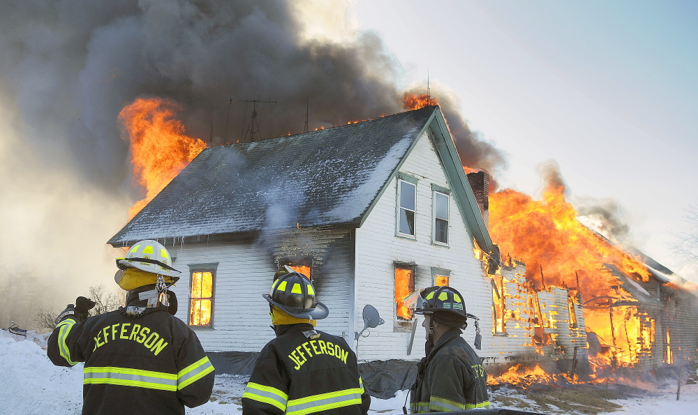 Jefferson firefighters assess a farmhouse that is fully engulfed in flames on Route 105 in Somerville on Sunday. Fire crews were able to rescue several animals at the farm before the fire overtook the barn.