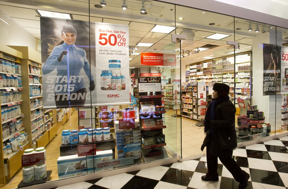 A woman walks past a GNC store Tuesday in New York. Numerous store brand supplements aren't what their labels claim to be, an ongoing investigation of popular herbal supplements has found.
