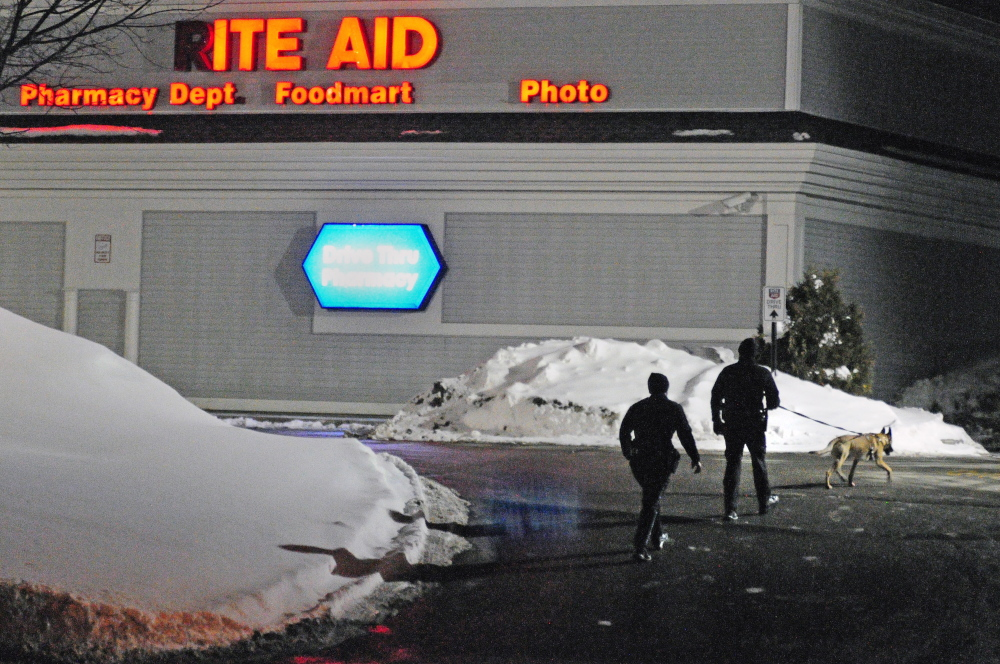 Two Augusta police officers and a tracking dog walk through the parking lot around 6:50 p.m. on Saturday after a robbery at the Rite Aid pharmacy at the corner of North Belfast Avenue and Bangor Street in Augusta.