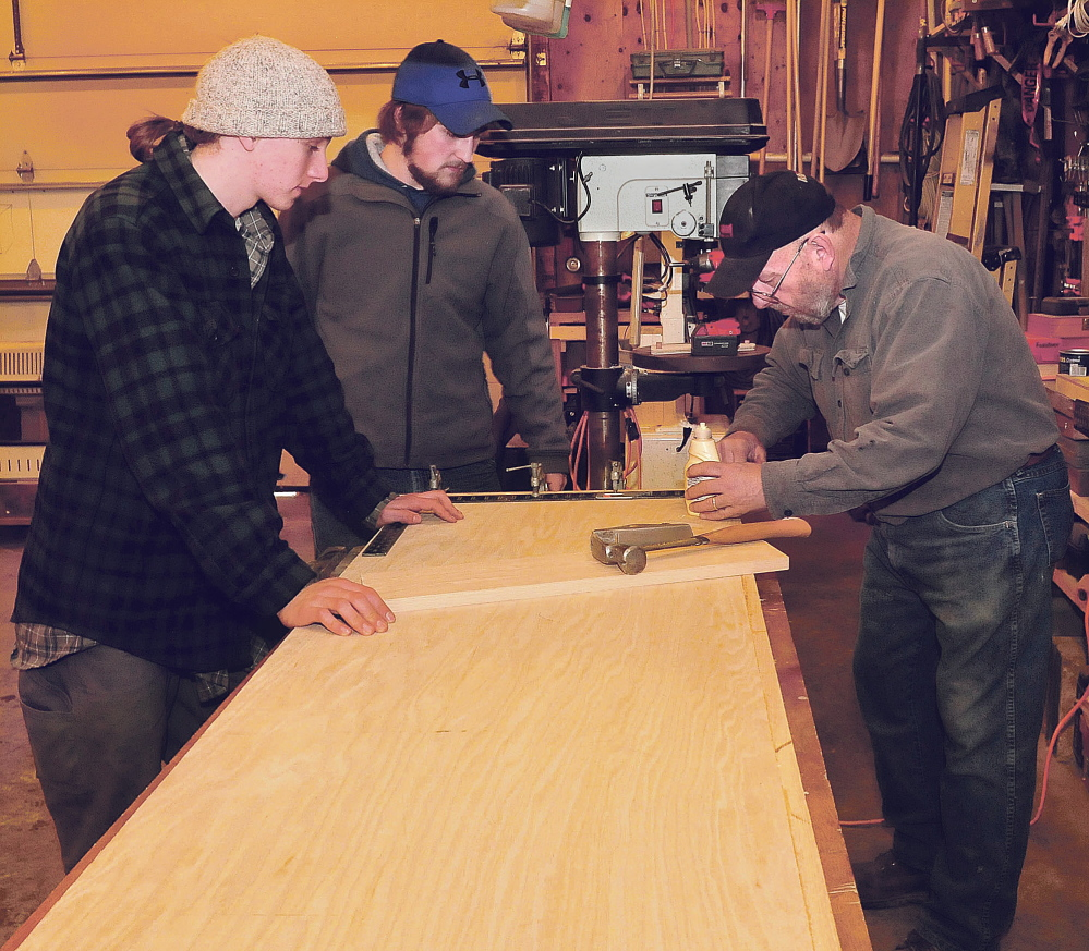 Carpenter Richard Tessier measures a countertop he and students Hannes Moll, left, and Issax Fletcher, of the Maine Academy of Natural Science made Tuesday in Skowhegan for radio station WXNX.