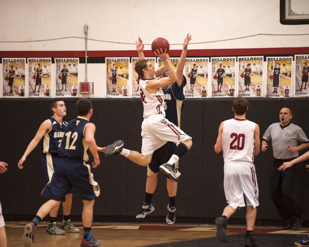 Hall-Dale's Wes LaPointe goes up for a shot as Traip's Angelo Succi (12) closes in to defend during a Western C prelim game Wednesday night.