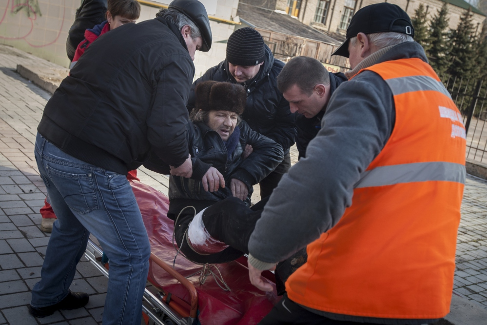 People and paramedics place a wounded man onto a stretcher after shelling between pro-Russian rebels and the Ukrainian government forces in Donetsk, Ukraine, Saturday.