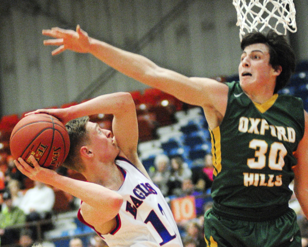 Messalonskee senior guard Trevor Gettig, left, shoots as Oxford Hills senior forward Patrick Marco defends during an Eastern A quarterfinal game Saturday at the Augusta Civic Center.