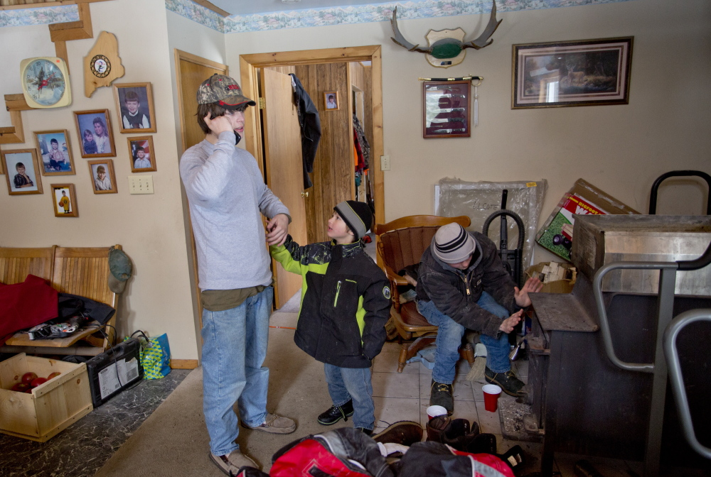 AT LEFT: Tyler Howard-Gotto talks on the phone with a reporter while his brother, Gauge Howard-Fowler, 4, tries to get his attention and friend Jonah May warms his hands by the wood stove at the camp owned by Tyler's grandfather in Andover.