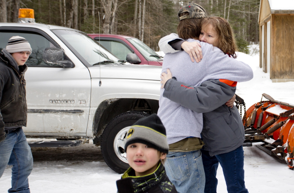 """Tyler Howard-Gotto, 15, hugs his aunt, Caroline Flynn, after Tyler returned safely to his grandfather's camp Tuesday along with his friend Jonah May, at far left. Tyler said he trusted the survival training he had received from his family and knew he and his friend would be fine if they kept their wits about them. """"You gotta keep calm in a survival situation,"""" Tyler said."""