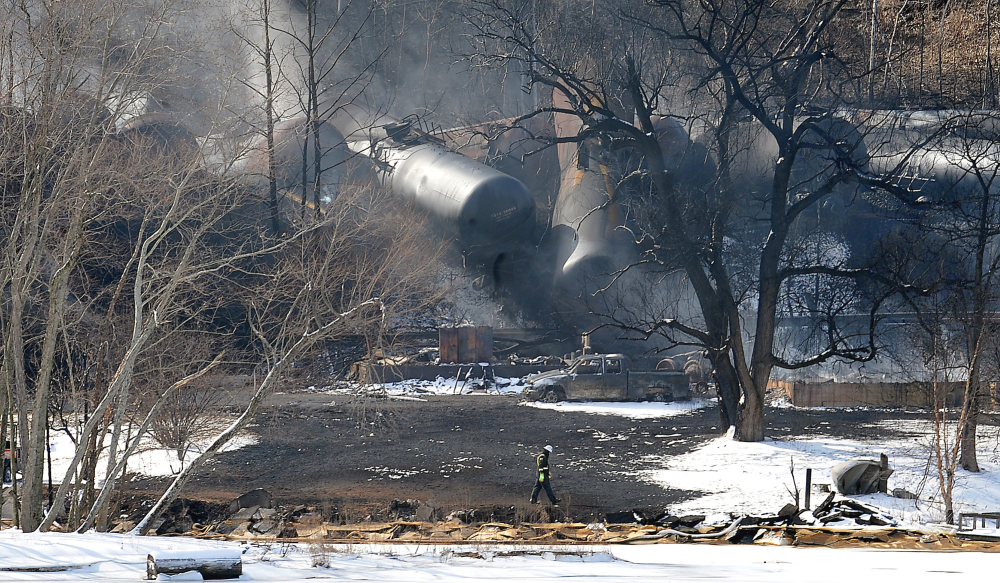 A crew member walks near the scene of the train derailment near Mount Carbon, W.Va., on Tuesday. A CSX train carrying more than 100 tankers of crude oil derailed in a snowstorm, sending a fireball into the sky and threatening the water supply of nearby residents.