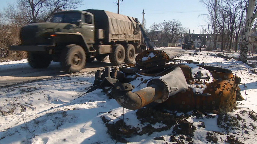 In this image made from TV, A truck drives past a destroyed tank as Russian backed rebel forces consolidate their position in Vuhlehirsk, Ukraine, Wednesday advancing on Debaltseve, about 4km (2 miles) from this position.