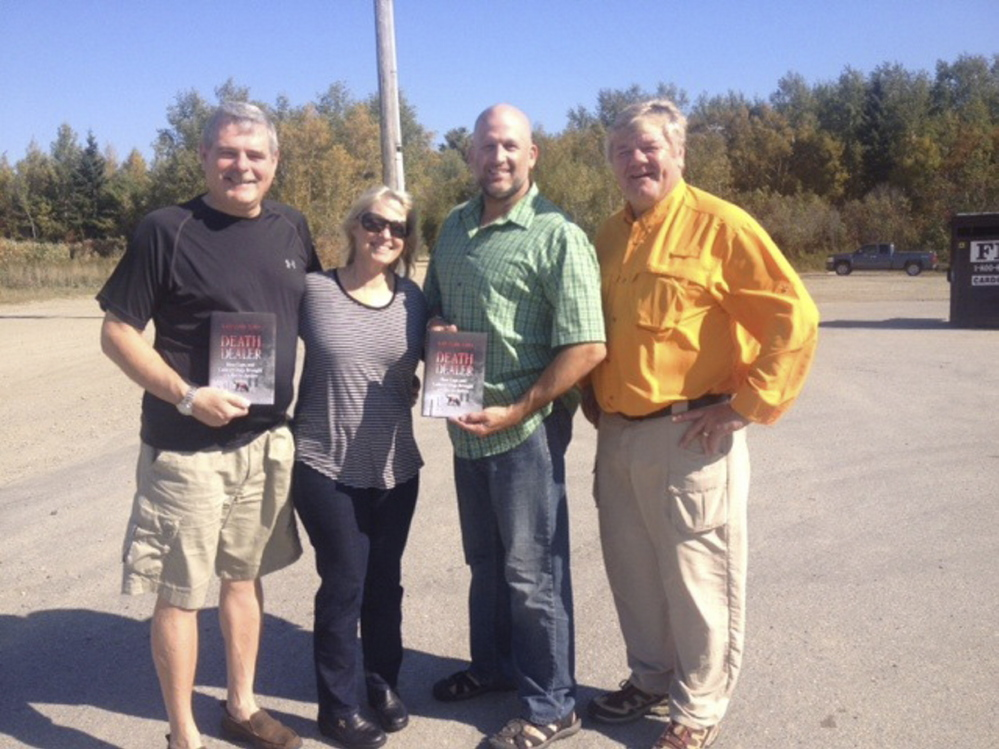 """Kate Flora, second from left, poses with """"Death Dealer"""" and, from left, Miramichi, N.B., Police Chief Paul Fiander, Deputy Chief Brian Cummings and Detective/Constable Dewey Gillespie. Flora's book details how the department and Maine Search and Rescue Dogs worked together to solve a murder."""