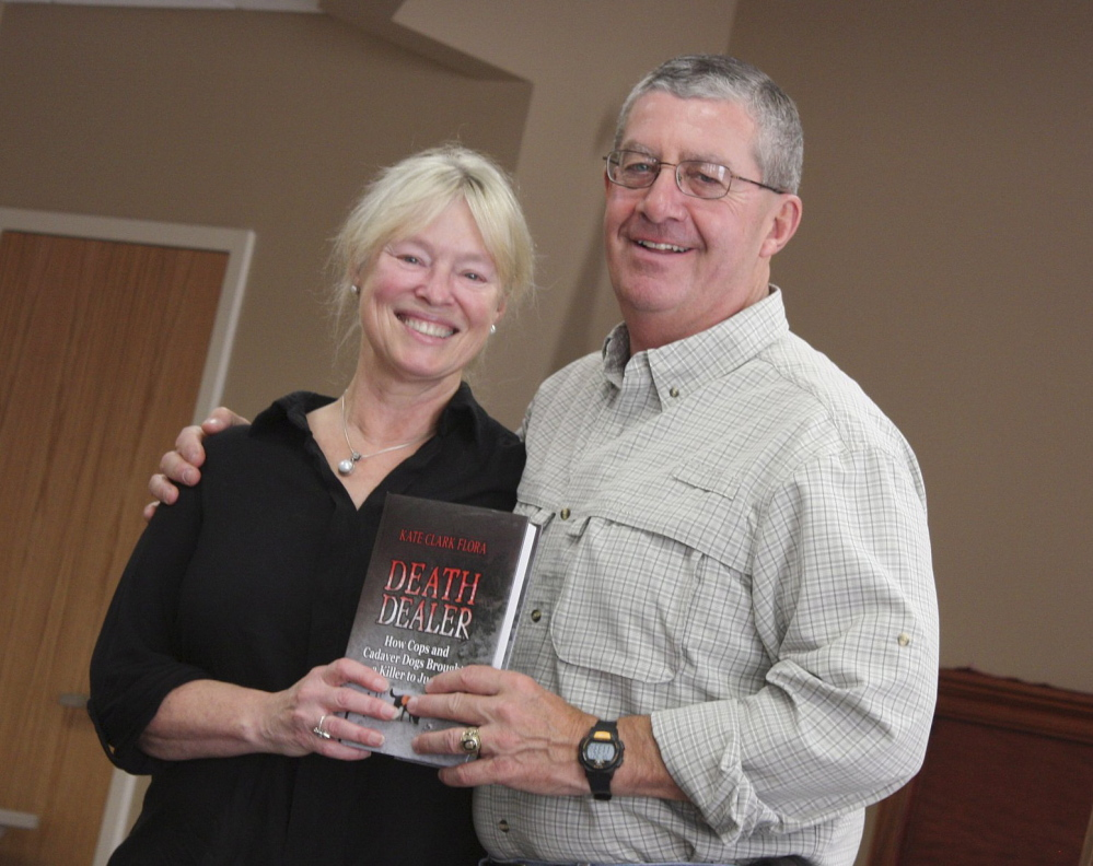 """Kate Flora, left, and Pat Dorian, retired as a lieutenant from the Maine Warden Service, show off her latest book, """"Death Dealer."""" The book chronicles how volunteers from Maine Search and Rescue Dogs helped solve a New Brunswick murder."""