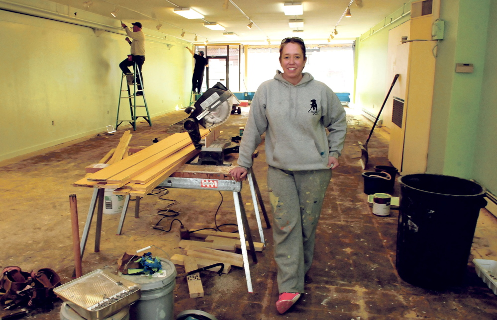 Loyal Biscuit Co. owner Heidi Neal takes a break from painting Wednesday with others at the business's new location, the former Earth Bound store in downtown Waterville.
