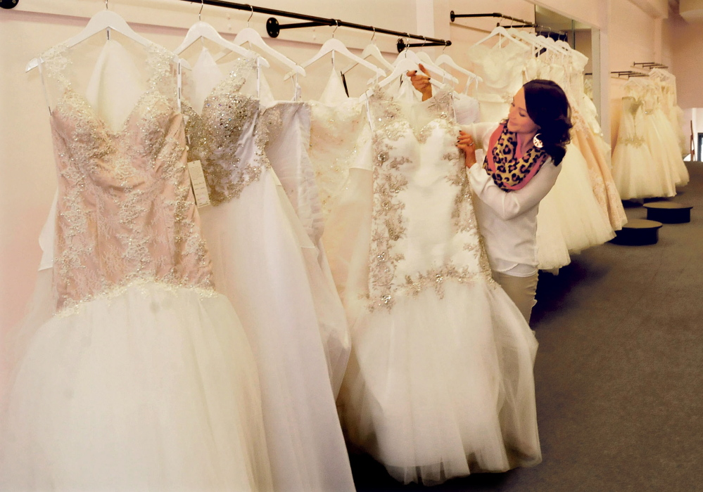 Linsey Gervais, owner of the La Belle Bridal Boutique, looks over her wedding dress inventory Wednesday at the store's new location, 48 Main St. in Waterville.