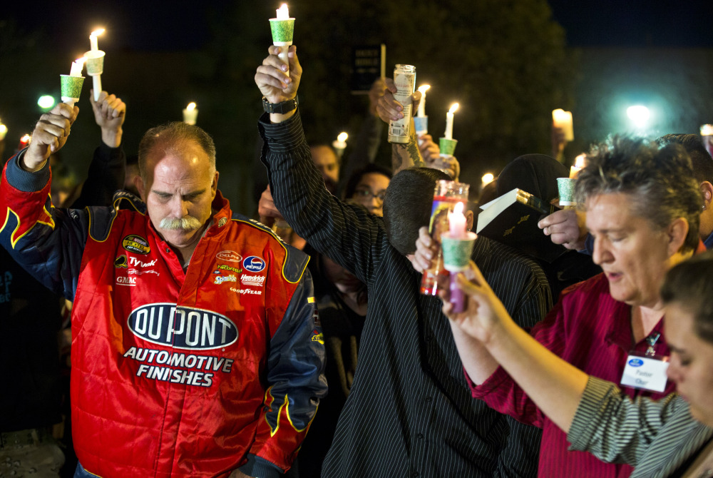 Robert Meyers, left, and others bow their heads during a prayer at a candlelight vigil Tuesday for his wife, Tammy, who was taken off life support on Saturday after a shooting in Las Vegas.
