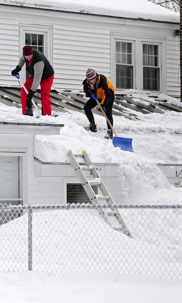 Tom Towle, left, and Debi Towle shovel off a roof on Thursday after an overnight snowstorm in Augusta.