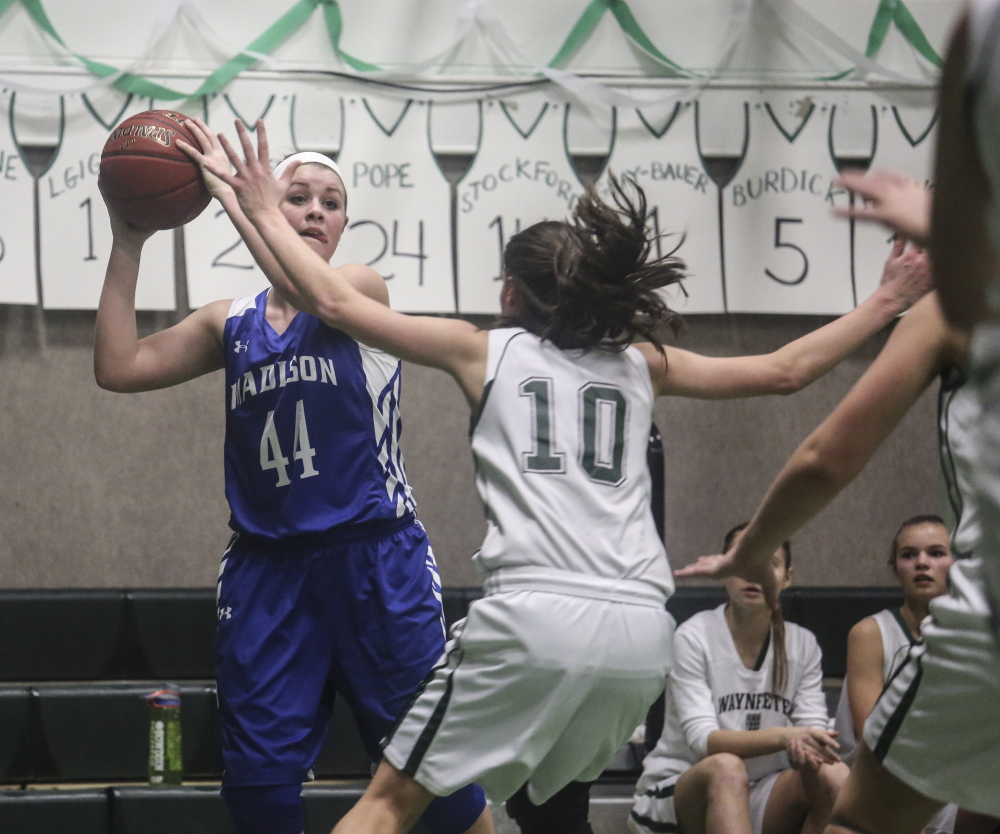 Madison forward Erin Whalen looks for an open teammate while Waynflete forward Julianna Harwood defends during a Western C prelim game Feb. 10 in Portland. The Bulldogs are one win away from reaching the regional finals.