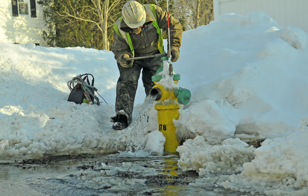 Darrell Field, a Kennebec Water District emmployee, bleeds the water lines as crews fix a water main break on Johnson Heights on Friday. District officials say the deep frost caused by the extreme cold this winter has been responsible for a number of broken water pipes in the area