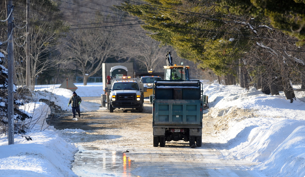 Crews from Kennebec Water District fix a water main break on Johnson Heights on Friday.
