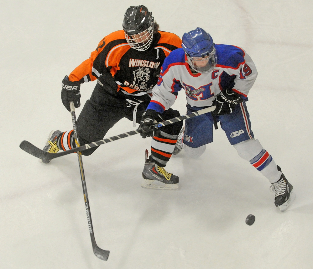 Messalonskee forward Jared Cunningham, right, battles for the puck with Winslow's, Jake Larson during an Eastern B game Jan. 10 at Sukee Arena. The Eagles enter the Eastern B playoffs as the No. 1 seed.