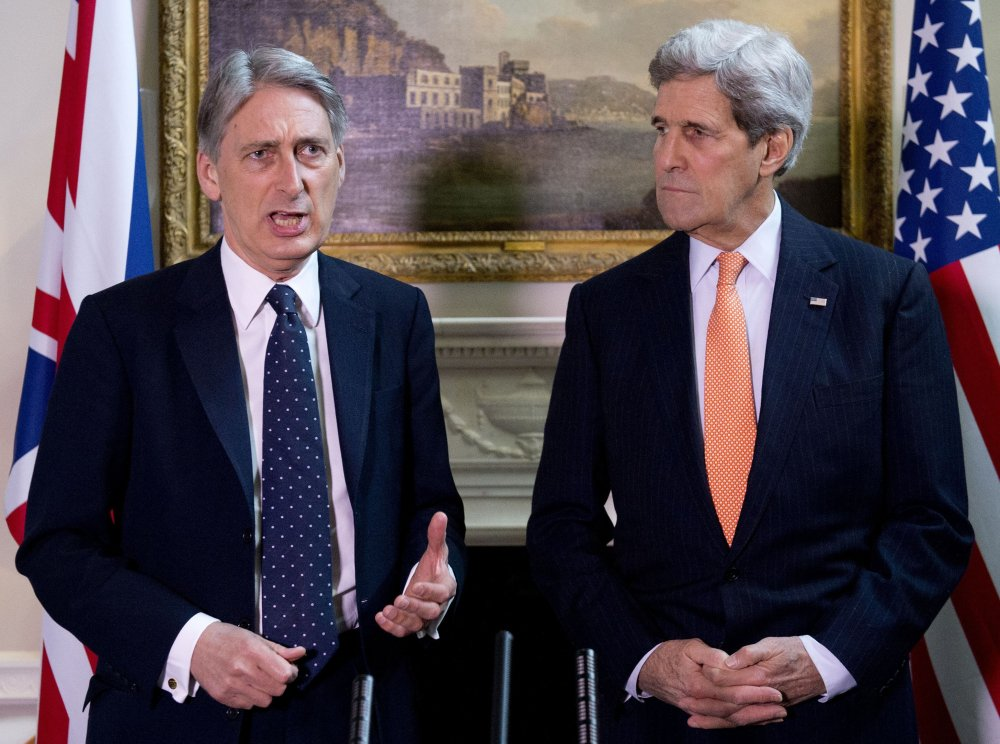 """U.S. Secretary of State John Kerry looks on during a press conference with Britain's Foreign Secretary Philip Hammond, left,  in central London on Saturday. Kerry, in London for talks with Hammond, said Russia's conduct was """"simply unacceptable"""" and that he expected to see agreement on further international sanctions in the coming days."""