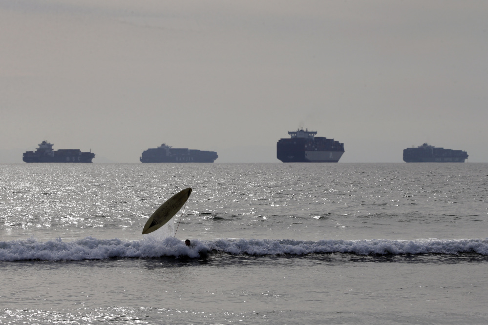 Jake Ferguson loses his surfboard while riding a wave, Friday, in Sunset Beach, Calif., as loaded cargo ships are anchored outside the Ports of Long Beach and Los Angeles.