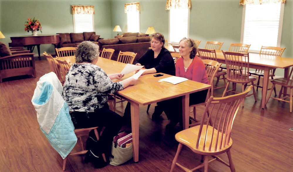 The New Hope Women's Shelter has re-opened in an expanded facility in Solon. Having a meeting on Wednesday in the Common Room are, from left, staff members Christine Greenlaw, Director Rebecca Philpot and Gale Beaulieu.