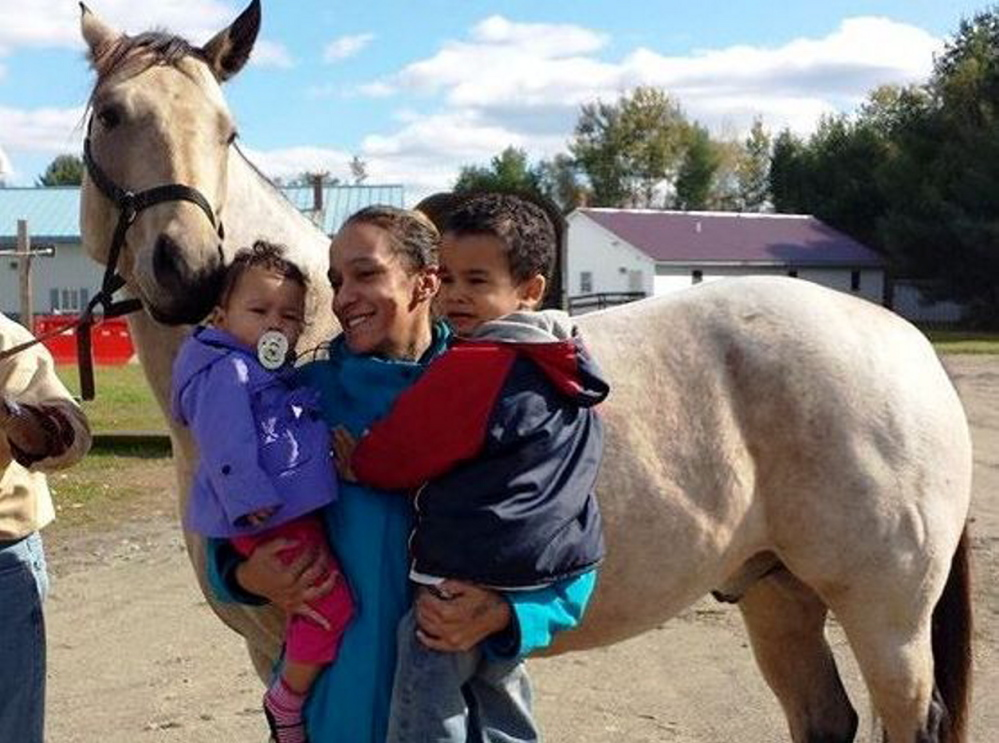 Nilsa Rodriguez, with her children, Jaylin, 1, and Joshua, 4, pose with a horse, Buckley, at the New Hope Women's Shelter in Solon. Rodriguez and her children have been staying at the shelter for about four months and hope to move to an apartment of their own at the end of the month.