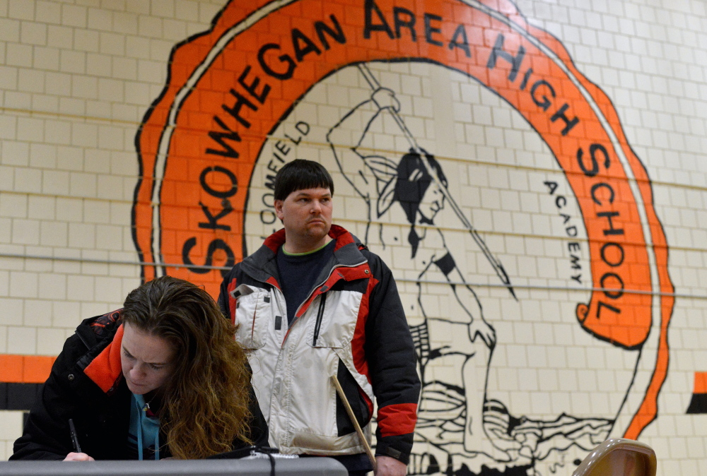 Ann-Marie Towle, 29, and her husband, Jeremy, both of Skowhegan, sign a petition to keep Skowhegan Area High School's Indian mascot Saturday at the FAB Fair at Skowhegan Area High School.