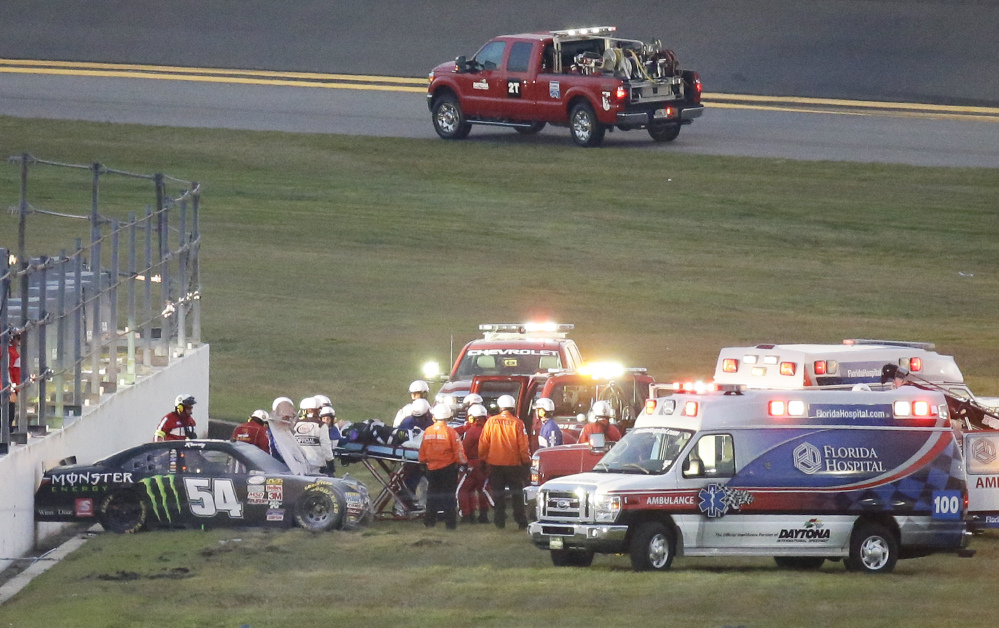 Kyle Busch, center, is taken to an ambulance on a stretcher after he was involved in a multi-car crash during the Xfinity series race at Daytona International Speedway on Saturday in Daytona Beach, Fla. Busch will miss Sunday's Daytona 500 due to injuries sustained in the crash.