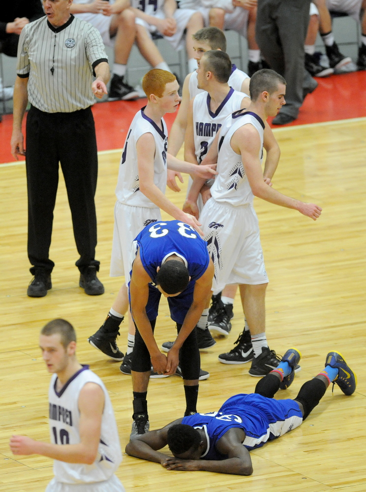 Lewiston High School's Quintarian Brown, 30, lies on the court as his teammate Isaiah Harris, 33, tries to help him up after fouling Hampden Academy's Nick Gilpin, 4, late in the fourth quarter of the Eastern A final on Saturday.