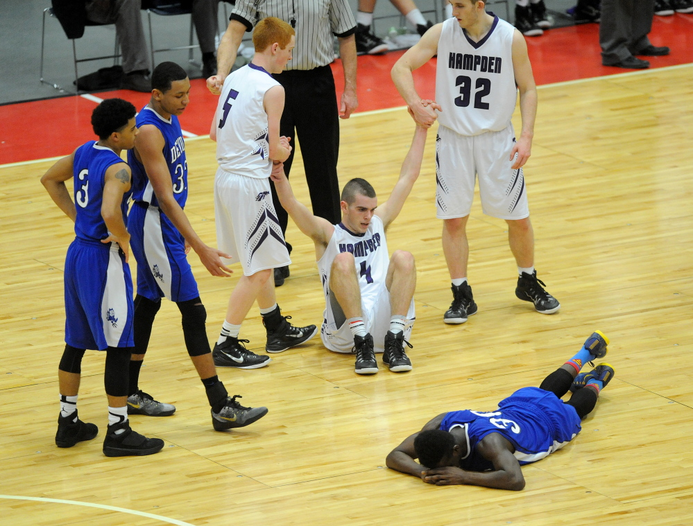 Quintarian Brown, 30, lies on the court after fouling Hampden Academy's Nick Gilpin, 4, late in the fourth quarter of the Eastern A championship game Saturday afternoon.