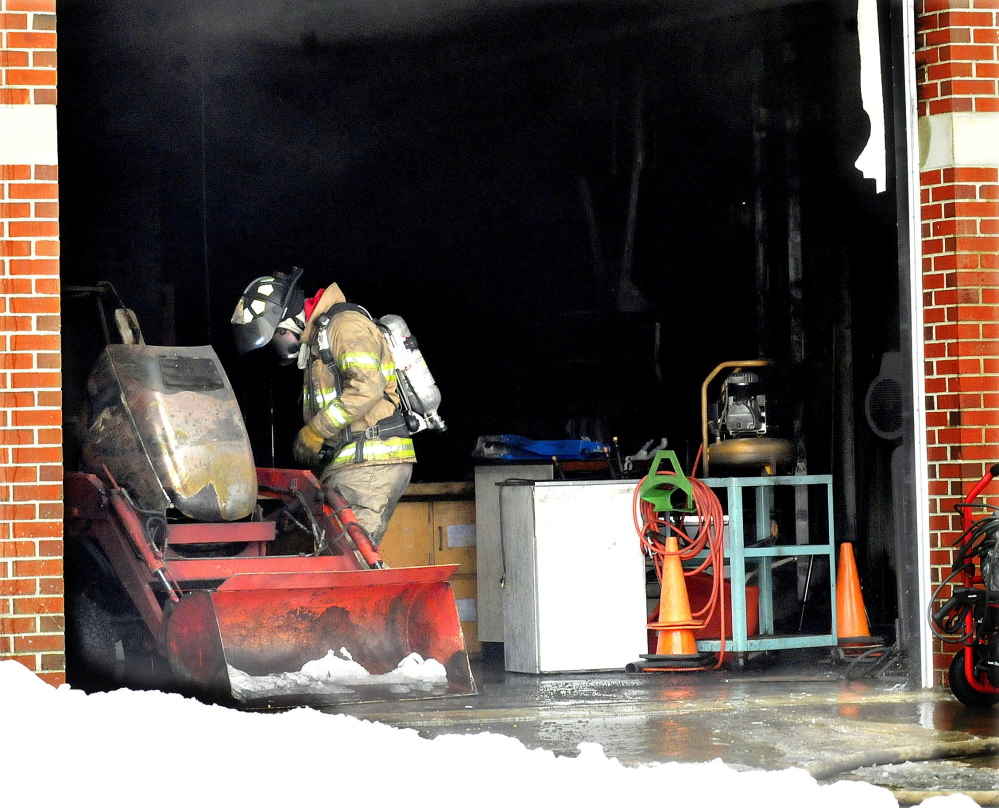 A firefighter looks over a small tractor that caught fire inside a garage attached to the Vassalboro Community School on Sunday. The fire did substantial damage to the garage and equipment, and firefighters from Vassalboro and Winslow had to use fans to ventilate other parts of the school fouled by black smoke.