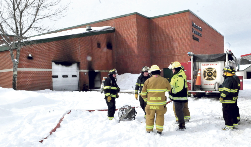 Firefighters from Vassalboro and Winslow wait as the Vassalboro Community School is ventilated of black smoke after a tractor caught on fire inside the attached garage, background, that caused substantial damage on Sunday