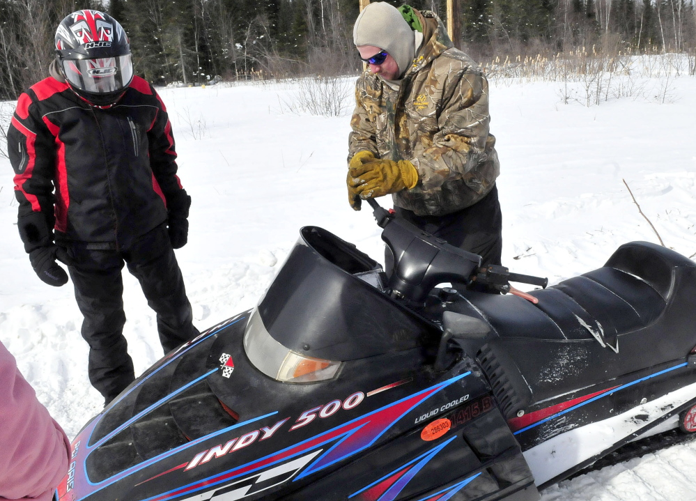 Patrick LaGross, right, of the Clinton Snowmobile club, turns the twisted steering wheel of the snowmobile on which Brittany Wentworth of Clinton was involved in an accident on a trail near Johnson Flat Road in Winslow. At left is Matt Lee of the Benton Snowmobile club, which towed the disabled snowmobile. Lee accompanied Wentworth on the snowmobiling trip and took her on his machine to meet rescue workers on the road.