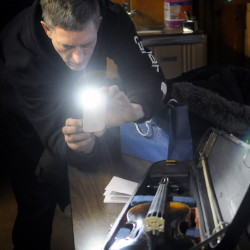 Mark Simpson photographs a violin that the Badershall family of Augusta arranged to get restored. The instrument was returned to the family Tuesday at American Legion Fitzgerald-Cummings Post 2 in Augusta. The instrument was made in 1850, according to a label found inside the body.
