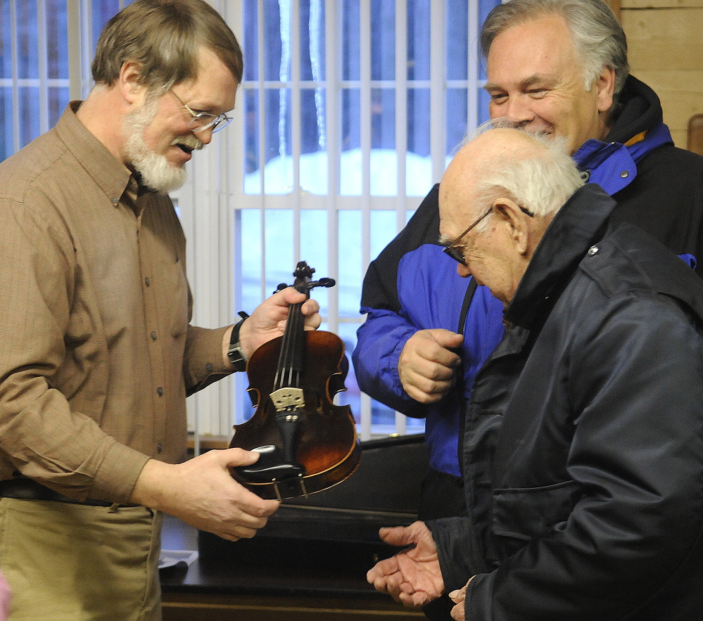 Nate Saunders hands a violin he restored recently to its owners, Roger C. Badershall, right, and his son, Roger E. Badershall, on Tuesday at American Legion Fitzgerald-Cummings Post 2 in Augusta.