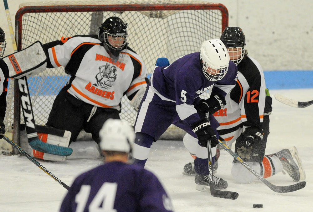 Winslow's Jake Larsen (12) defends Hampden's Jordan Dysart (5) as goalie Andrew Beals defends.
