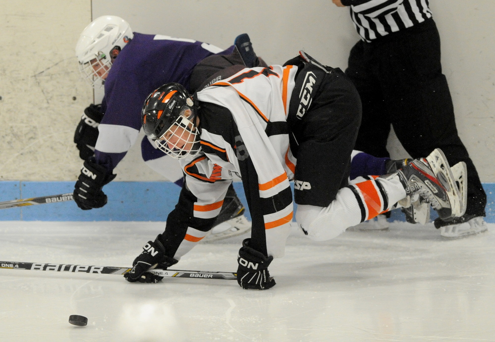 Winslow High School's Jacob Trask (16) battles for the puck with Hampden's Jordan Dysart during an Eastern B quarterfinal Tuesday at Sukee Arena in Winslow. The Black Raiders won 3-2.
