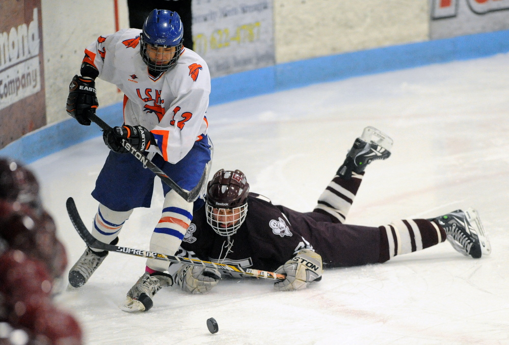 Staff photo by Michael G. Seamans   Lawrence/Skowhegan's Alex Paul (12) skates away from Edward Little's Ryan Raby (25) during an Eastern A quarterfinal Tuesday night at Sukee Arena.