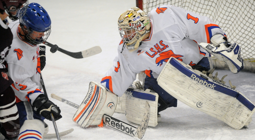 Staff photo by Michael G. Seamans   The puck hovers in front of Lawrence/Skowhegan High School's Samuel Haver (13) as goalie Curtis Martin (1) tries to make the save during an Eastern A quarterfinal Tuesday night at Sukee Arena.