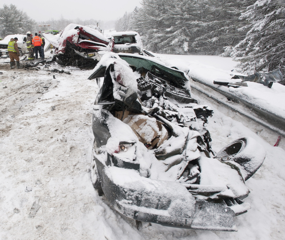 a;kljsfd;ljl;kj .... Carmel, Maine-02-25-2015-- Bangor Police detective Larry Morrill sips coffee as he walks among the wreckage of a mutiple car pileup on intersate 95 in Carmel. Morrill was involved in his personal vehicle. The car in the left of the frame was under the school bus when police arrived. The driver escaped with only scratches according to people who helped him out of the car. Kevin Bennett Photo