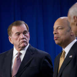 Former Homeland Security Secretary Tom Ridge listens at left as current Homeland Security Secretary Jeh Johnson speaks during a news conference in Washington on Wednesday. Johnson said that without legislation to set new spending levels, there would be no money for new initiatives.