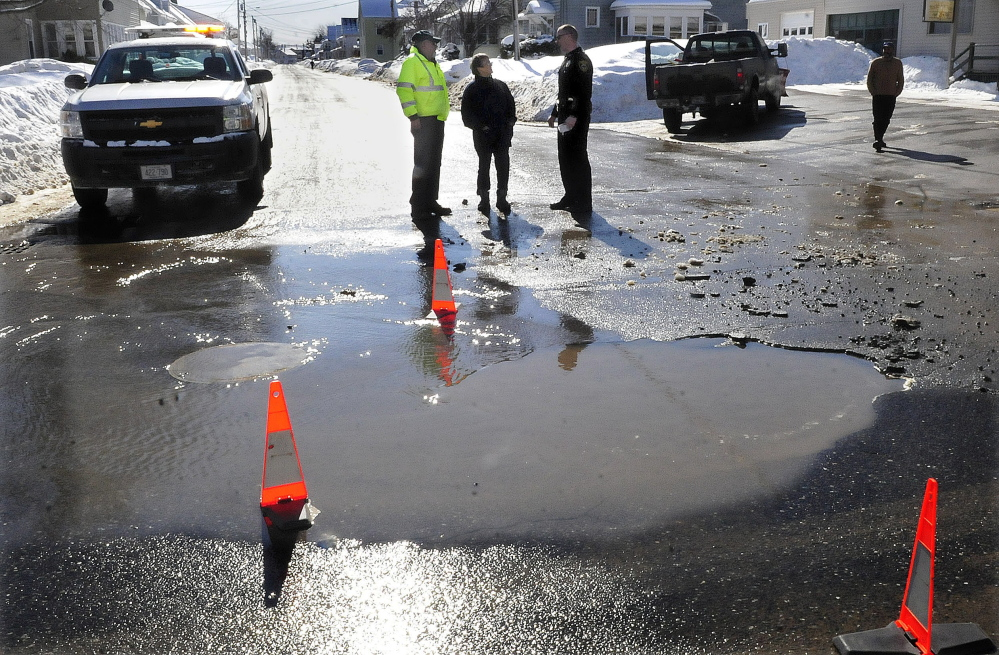 """Motorist Muriel Rancourt, center, speaks with Winslow Public Works Director Paul Fongemie, left, and officer John Veilleux after her car drove over a water-filled sinkhole beside Monument Street on Wednesday. The hole, three to four feet deep,  was created by a broken water line on Clinton Avenue. """"I couldn't believe it when I hit that,"""" Rancourt said while waiting for a tow truck. Fongemie said at least six vehicles hit the hole, leaving several with flat tires. The street was closed to traffic Wednesday afternoon while crews from Kennebec Water District repaired the broken pipe."""