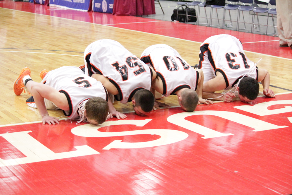 Forest Hills seniors, from left, Ryan Petrin, Tanner Daigle, Brandon Ouellette and Matt Turner, kiss the Augusta Civic Center floor after the Tigers won the Western D championship last weekend. Forest Hills has made it a tradition to kiss the Civic Center floor after it wins a title.