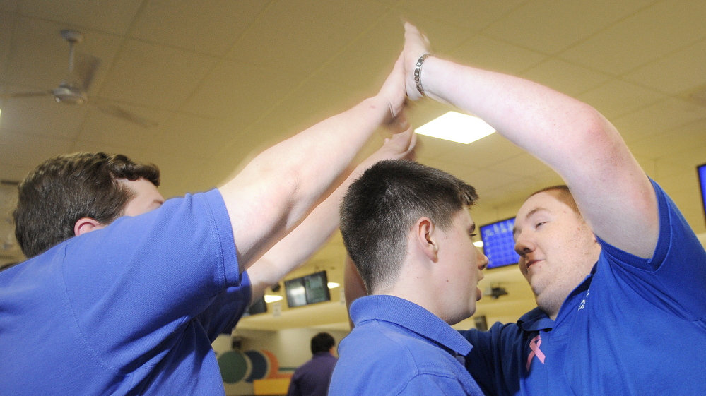 Tresten Bergeron, right, salutes Lawrence teammates during a match Wednesday at Sparetime Recreation in Hallowell. Bergeron recently won the individual state bowling championship.