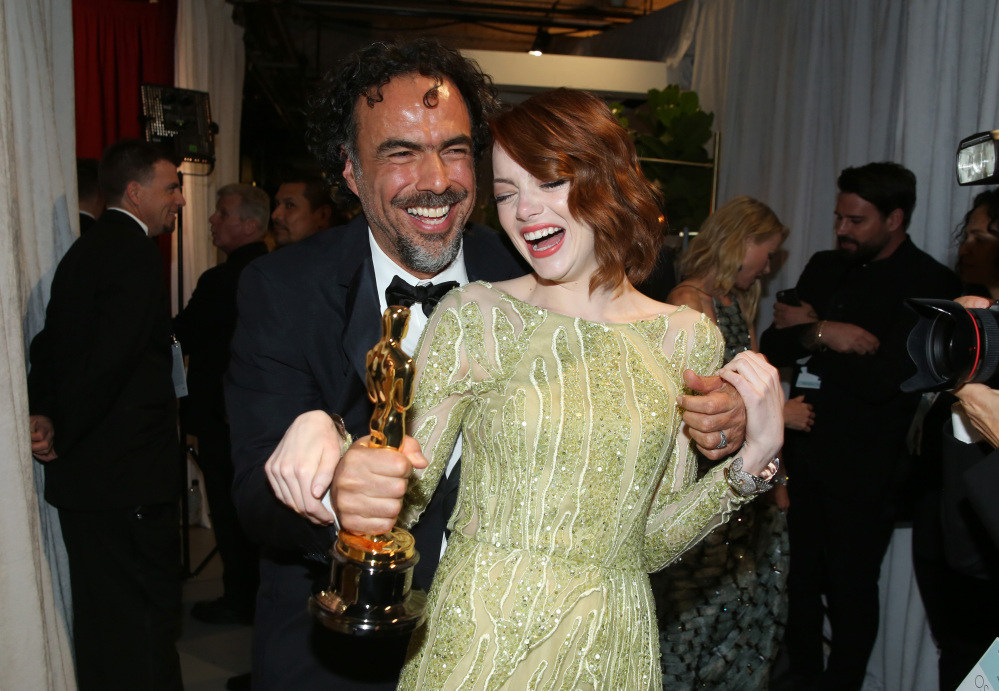 Alejandro Gonzalez Inarritu, left, and Emma Stone are seen backstage at the Oscars on Sunday at the Dolby Theatre in Los Angeles.