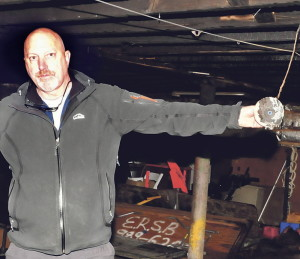 Tom Davis, owner of the Are You Ready to Party? shop in Waterville, holds the smoke alarm he credits for the swift response by the fire department to put out the basement fire that caused substantial damage to the business on Wednesday.