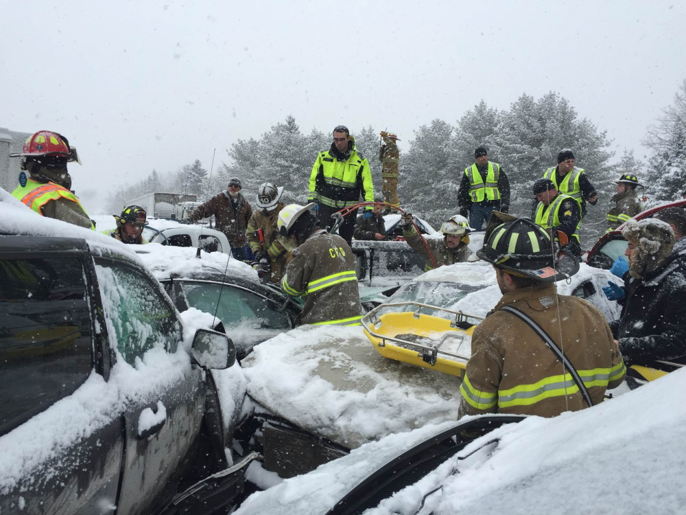 Firefighters wait with a stretcher while rescue workers struggle to cut open  a car to extricate a victim of  a pile-up on Interstate 95 in Etna on Wednesday