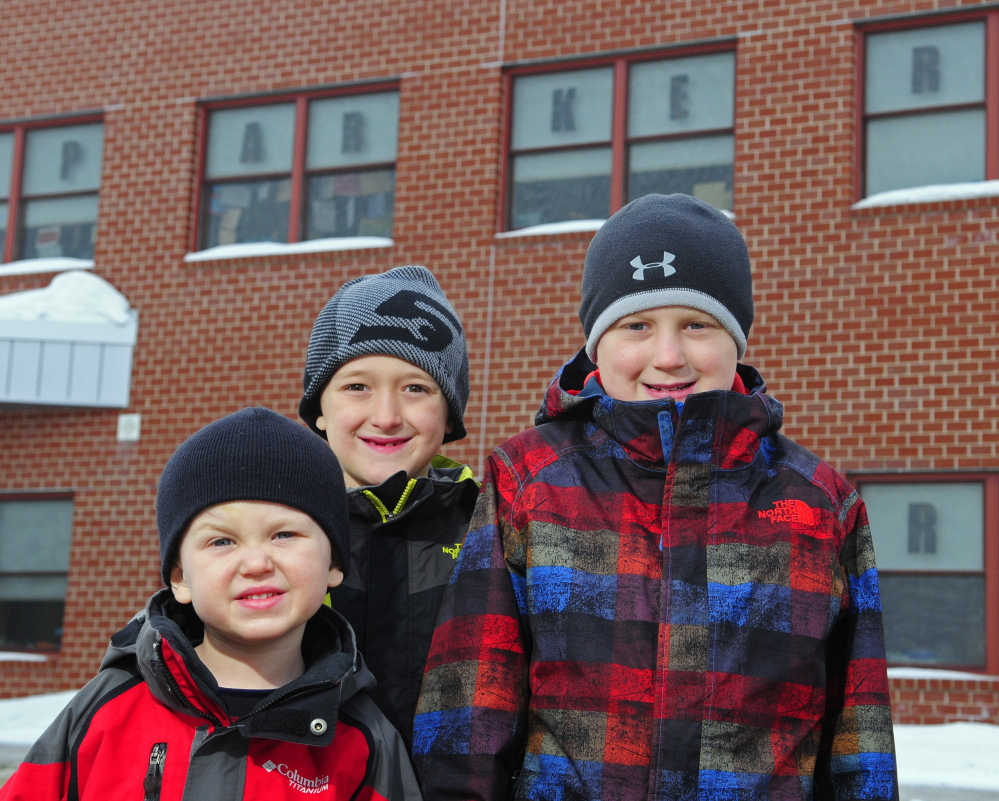 Parker St. Onge, right, stands with his brothers Emory, left, and Anderson, center, in front of the Parker Power sign in the windows on Thursday at Windsor Elementary School. The words are in windows on both sides of the school.