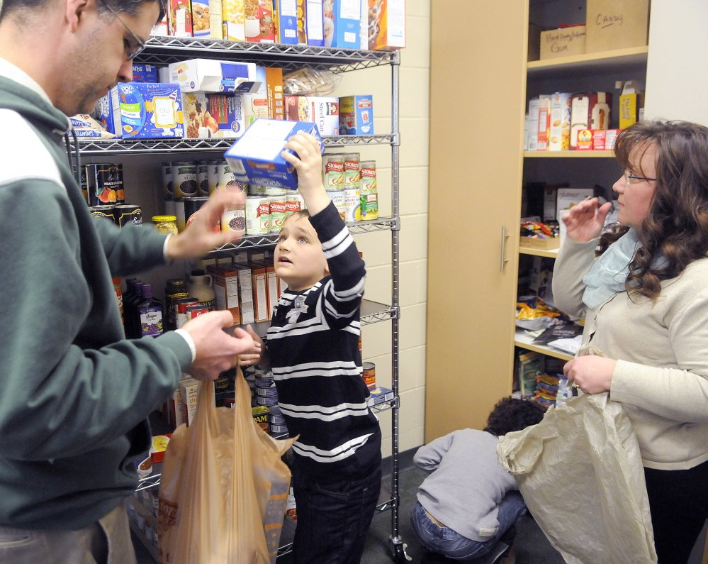 Chelsea School student Mitchell Dusoe loads a bag of groceries Thursday with Principal Andrew Doiron in the school's food bank. Students in need of additional food are welcome to bring the bags home with them. Dusoe and fellow student Jaydyn Lachzik helped Doiron and school secretary Leslie Burgess, right, fill several bags for students who need supplemental food.