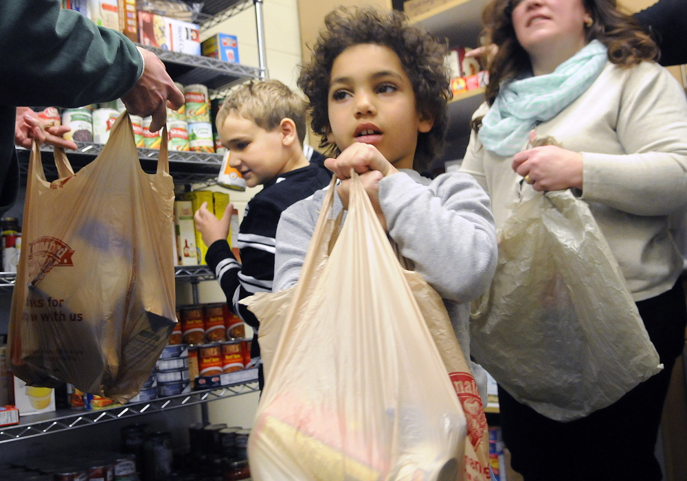 Chelsea School students Jaydyn Lachzik, right, fills a bag of groceries Thursday with fellow student Mitchell Dusoe at the school's food bank. Students in need of additional food are welcome to bring the bags home with them. The children filled several bags for classmates.